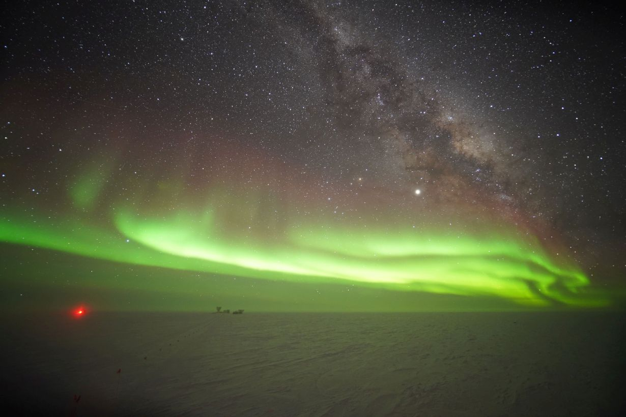 Polar light above the South Pole. The red point is the IceCube Laboratory. The neutrino experiment proper is installed several kilometers deep in the ice. (Photo: Kathrin Mallot, IceCube, NSF)